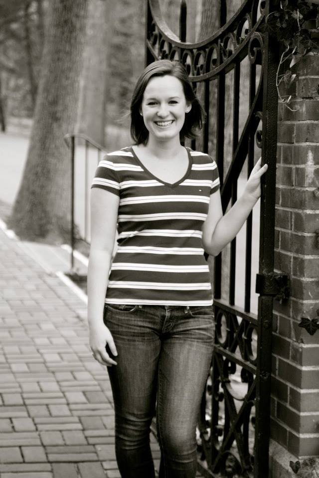 Senior portrait of me (Leah Tams). It is a black and white photo, and I'm standing at an iron gate next to a brick wall on Mary Washington's campus.